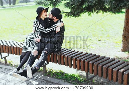 Man and pregnant girl sitting on bench in park. Hugging, looking at each other. Young couple, love story, pregnant girl. Outdoors, full body