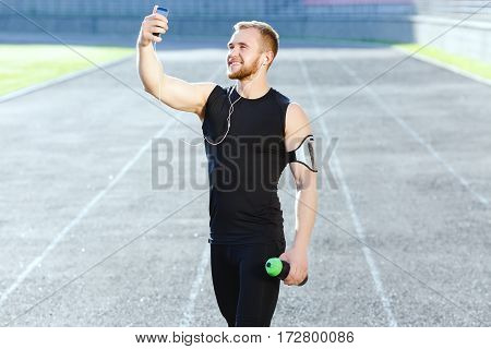 Man taking stop after running on track, looking at phone and making selfie. Sportsman in black training suit listening to music and holding dumbbell. Outdoors, stadium, profile