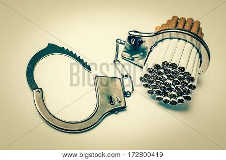 Cigarettes and handcuffs - smoking addiction concept on white background - retro style