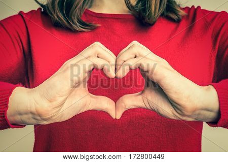 Female hands showing sign of heart on red jumper - retro style