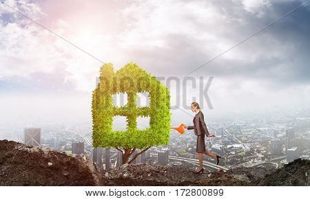 Young attractive businesswoman watering house shaped plant in ground with can against the backdrop of the city