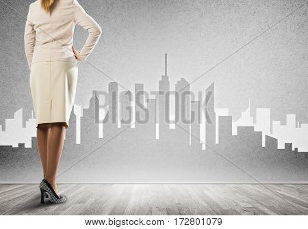 Back view of businesswoman and sketches of construction project on wall