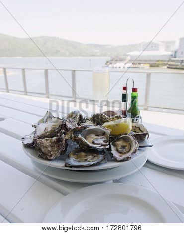 A Plate Of Fresh Open Oysters And A Glass Of Champagne On A White Table With A View Of The Ocean, Se