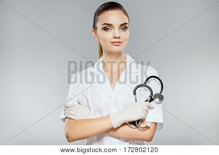Beautiful nurse with nude make up wearing white medical robe and holding stethoscopes at gray background, looking at camera, health care and pharmacology concept, girl on white uniform.
