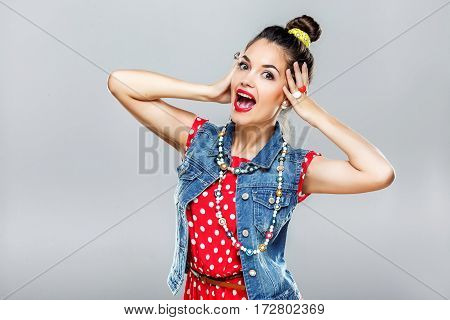 Gorgeous girl with dark hair and red lips wearing red dress and jeans sleeveless posing at gray studio background, portrait, fashion.