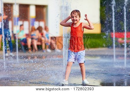 Excited Boy Having Fun Between Water Jets, In Fountain. Summer In The City