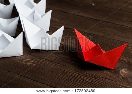 Set of origami boats on wooden table, one red and the rest all white.