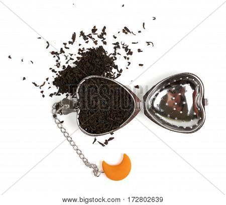 Putting black tea in the tea strainer. Isolated on white