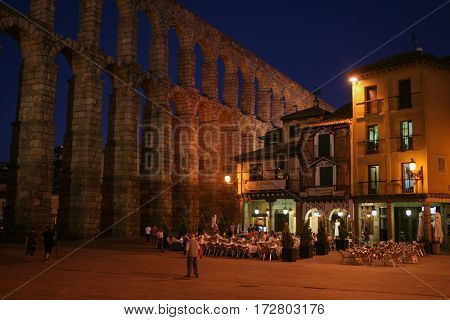 SegoviaSpain-July 24: Street cafe near roman aqueduct in the evening in Segovia, Spain-on July 24, 2009