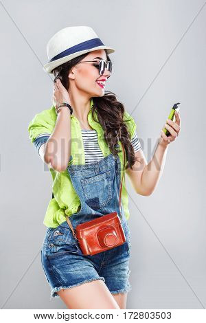 Gorgeous tourist girl with dark hair and red lips wearing white hat and sunglasses, posing at gray studio background with mobile phone and smiling.