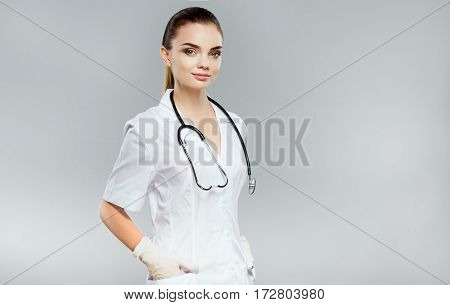Beautiful nurse with brown hair and nude make up wearing white medical robe and stethoscopes at gray background and looking at camera, health care and pharmacology concept, girl on white uniform.