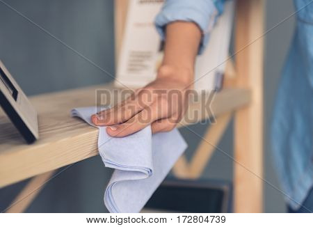 Cropped image of beautiful young woman using a rag while cleaning furniture at home
