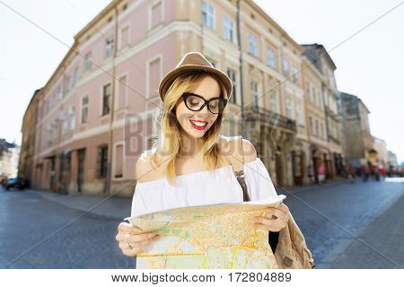 Gorgeous  tourist girl with light hair and red lips wearing hat and glasses, holding map at old European city background, portrait.