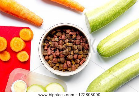Set of animal dry food with fresh vegetables and eggs on white kitchen table background top view