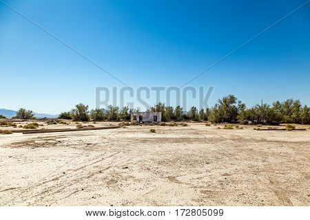 An abandoned building sits alongside the roadway near Death Valley Junction in the Funeral Mountains Wilderness Area California.