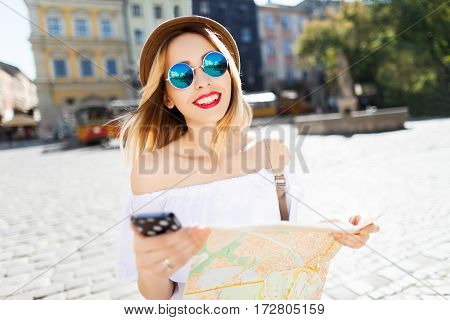 Smiling tourist girl with light hair and red lips wearing hat and glasses, holding map at old European city background, portrait.