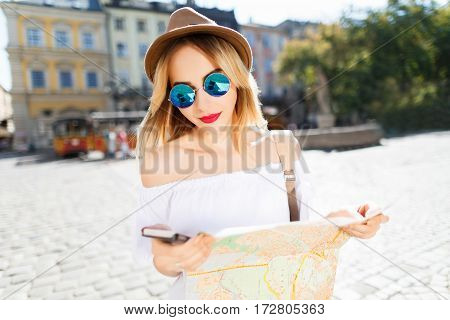 Young tourist girl with light hair and red lips wearing hat and glasses, holding map and mobile phone at old European city background and smiling, sunny weather.