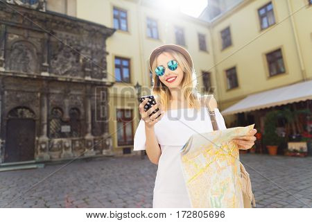 Cute tourist girl with light hair and red lips wearing hat and glasses, holding map and mobile phone at old European city background and smiling, sunny weather.