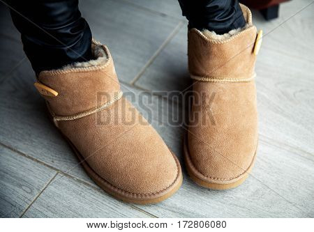 Girl in brown ugg boots in leather pants. Fashion style modern. Grey wood floor