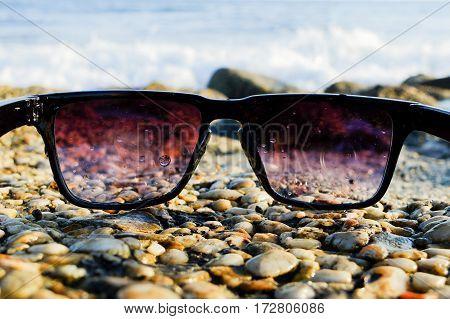 Black sunglasses lying on wet rocks near sea, close up, summertime.