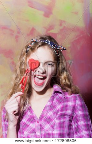 Excited Pretty Girl Laughs With Red Heart On Stick