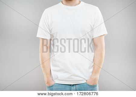 Man in white T-shirt and jeans. Mockup. Hands in pockets. Portrait without head. Indoors, studio