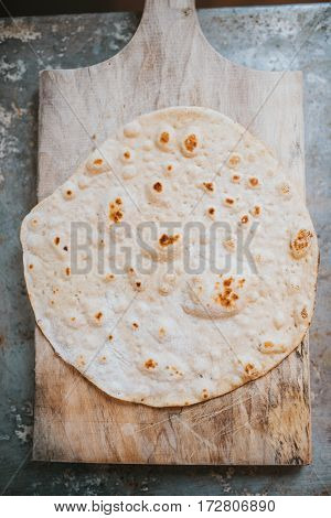 Homemade whole wheat flour tortilla on wooden board on metal table