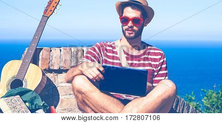 Young man travel portrait using notebook on hill top ocean background - Globe trotter hipster guy with sun glasses and pc relaxing on summer day outdoors - Concept of freedom with blue vintage filter