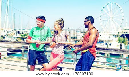 Three spotive friends resting after sports exercise outdoors on bridge at city riverside - Happy american joggers having relaxing break outside on summer sunny day - Vintage filter