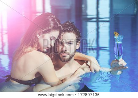 wet couple of pretty woman or sexy girl and handsome bearded man or guy with muscular body in swimming pool with blue water holds cocktail glass