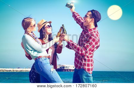 Friends happy moments drinking beer at beach full moon night party - Joyful students having fun taking selfie with cheers bottle on summer holiday