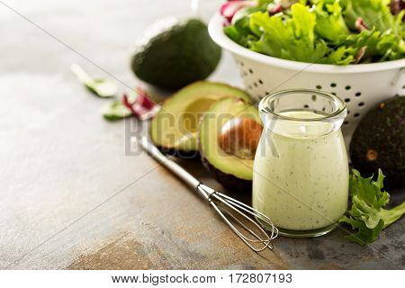 Avocado ranch dressing in small jar with salad leaves in a collander with copy space