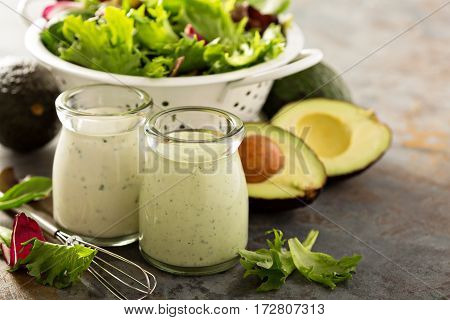 Avocado ranch dressing in small jar with salad leaves in a collander