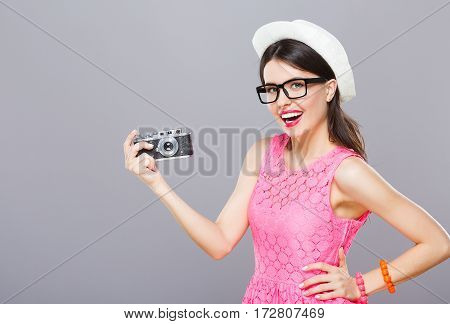 Beautiful young girl with dark hair and red lips wearing pink dress and sunglasses posing with camera at gray studio background, portrait, copy space.