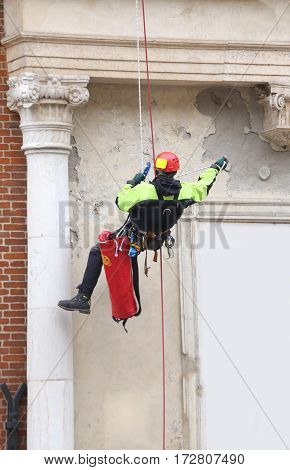 Brave Firefighter Climbing With Ropes  On An Old Building To Mon