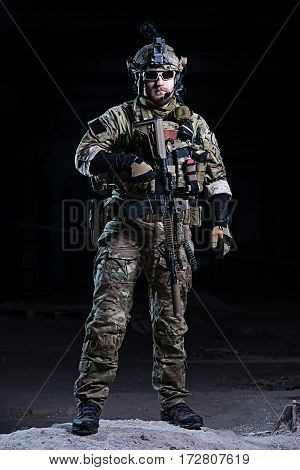 Spec ops soldier in uniform with weapon wearing glasses helmet with night vision device