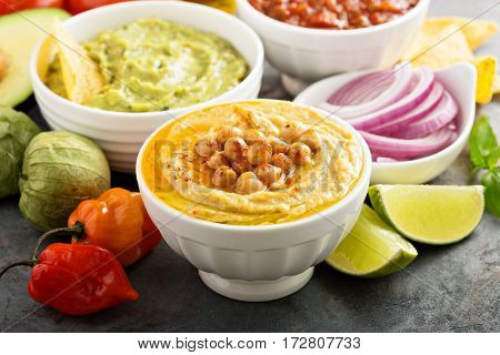 Guakamole and hummus dips with vegetables copy space
