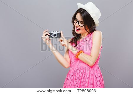 Pretty young girl with dark hair and red lips wearing pink dress and sunglasses posing with camera at gray studio background, portrait, copy space.