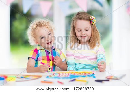 Little boy and girl draw together in white room with window. Kids doing homework painting and drawing. Children paint with paintbrush color and pencils. Art and crafts for toddler and preschooler.