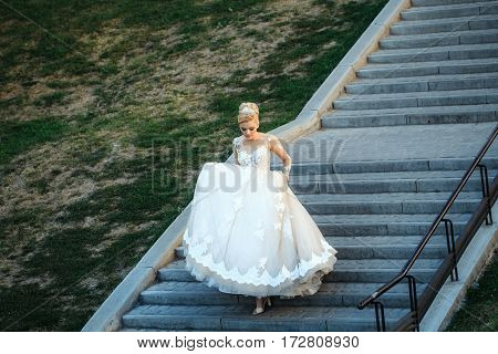 Pretty Girl Or Cute Bride Walking Down Grey Stairs