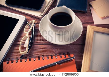 Still life photo of tablet, notepad, coffee and glasses and other stuff on wooden table.