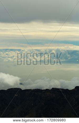 Idyllic black volcanic mountain tops rocky peaks under white clouds on blue sky background