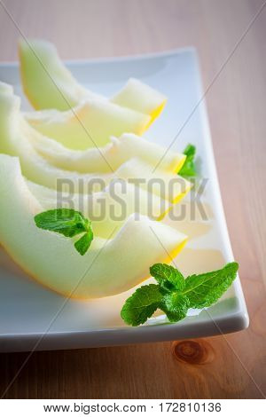 Fresh ripe honeydew melon slices on the plate