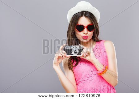Portrait of young girl with dark hair and red lips wearing pink dress and sunglasses posing with camera at gray studio background.