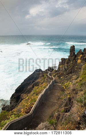 stairs on empty rocks north coast of Tenerife near the town of garachico with view over atlantic ocean and blue sky