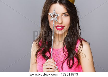 Cute young girl with dark hair and red lips wearing pink dress posing with magic stick at gray studio background, portrait.
