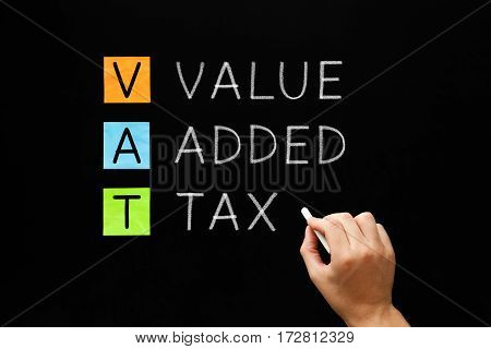 Hand writing VAT - Value Added Tax with white chalk on blackboard.
