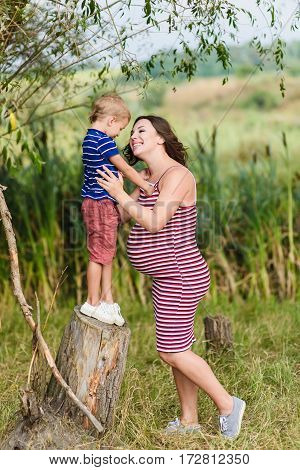 Pregnant mother and her son playing together. Happy mother and her son. Green background blurred, outdoors.