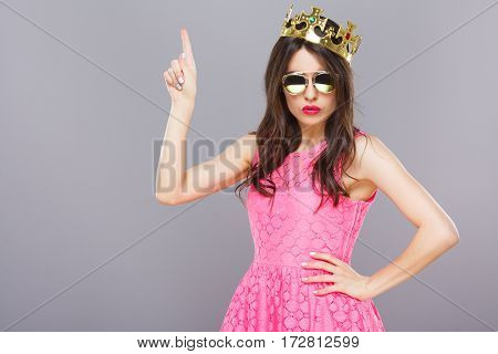 Nice young girl with dark hair and red lips wearing pink dress, sunglasses and crown posing at gray studio background, portrait, copy space.