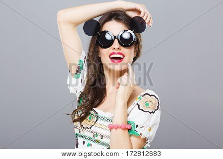 Girl in black round sunglasses with side glasses. Looking at camera, smiling widely. Hand on head, another touching chin. Summer outfit. Head and shoulders, studio, indoors